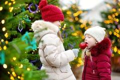 吃红色苹果的两个可爱的妹盖用在传统圣诞节市场上的糖结冰 免版税图库摄影