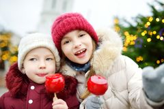 吃红色苹果的两个可爱的妹盖用在传统圣诞节市场上的糖结冰 库存图片