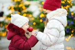 吃红色苹果的两个可爱的妹盖用在传统圣诞节市场上的糖结冰 图库摄影