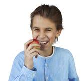 吃红色苹果的年轻男孩 免版税库存图片