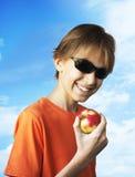 吃红色苹果的年轻男孩 库存图片