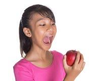 吃红色苹果计算机II的年轻亚裔马来的少年 免版税库存图片