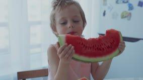 吃红色西瓜和汁液的愉快的男孩流动在牙下 股票录像