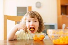 吃红萝卜沙拉的小女孩 免版税图库摄影