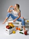 吃红萝卜的妇女在有新鲜的有机菜的箱子附近 免版税库存照片