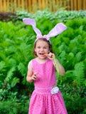 吃红萝卜的小女孩佩带的兔宝宝耳朵 免版税库存照片