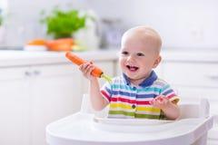 吃红萝卜的小婴孩 免版税库存照片
