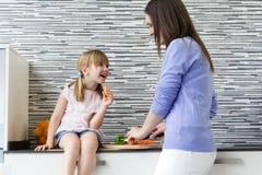 吃红萝卜的少妇和小女孩在厨房里 免版税库存图片
