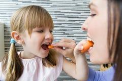 吃红萝卜的少妇和小女孩在厨房里 免版税库存照片