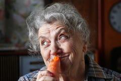 吃红萝卜的微笑年长妇女 库存图片