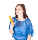 吃红萝卜的快乐的妇女纵向,查出在空白背景 免版税库存图片