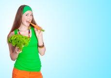 吃红萝卜的快乐的妇女画象 免版税库存图片