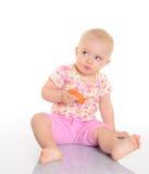 吃红萝卜的甜矮小的婴孩坐在白色的楼层 免版税库存图片