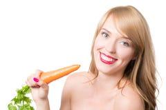 吃红萝卜的年轻愉快的妇女 库存图片