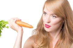 吃红萝卜的年轻愉快的妇女 免版税库存图片