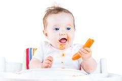吃红萝卜的滑稽的女婴尝试她的第一种固体 免版税库存图片