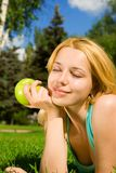 吃绿色俏丽的妇女的苹果 库存图片