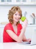 吃绿色厨房妇女的苹果 库存图片