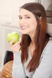 吃绿色厨房妇女的苹果 免版税图库摄影