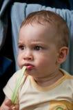 吃绿色大黄的婴孩 免版税库存图片