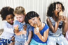 吃美味的冰淇凌的小孩 免版税库存图片