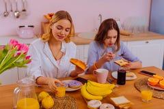 吃美味的新月形面包的姐姐享用与兄弟姐妹的早餐 库存照片