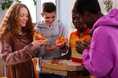 吃美味的比萨的四个少年在学习以后 库存图片
