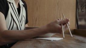 吃美味的面条的白种人妇女在有筷子的一家地方中国餐馆 股票录像