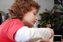 吃肉少年的男孩 免版税库存图片