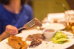 吃肉用沙拉的女孩在餐馆 免版税图库摄影