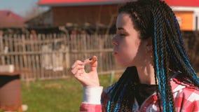 吃肉香肠的少妇在后院在春天在一个晴天 她的儿子戏耍 影视素材