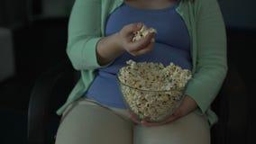 吃肥胖的妇女采取极少数从碗的玉米花和,当观看电影时 影视素材