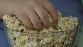 吃肥胖的孩子采取极少数从碗的玉米花和,驱散它  股票录像
