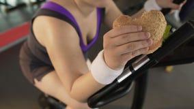 吃肥腻汉堡的超重女性,当骑固定式自行车,生活方式时 股票视频