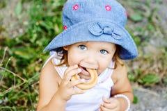 吃脆煎肉片的小孩女孩 免版税库存照片