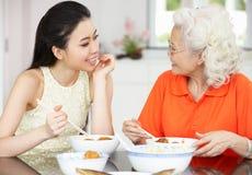 吃膳食的中国母亲和成人女儿 库存图片