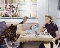 吃膳食的妇女在桌上用活火鸡(所有人被描述长期不活,并且庄园不存在 供应商保单 免版税库存图片
