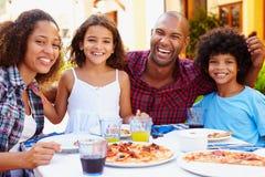 吃膳食的家庭画象在室外餐馆 免版税库存图片