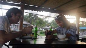 吃膳食的愉快的年轻夫妇在夏日喝在显示某事在她的智能手机的户外咖啡馆和女孩的啤酒 股票视频