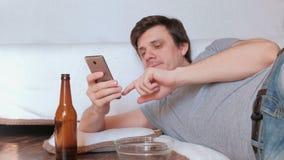 吃芯片和喝啤酒的英俊的年轻人学士和浏览他的手机 股票视频
