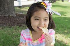 吃芯片的一个逗人喜爱的小女孩,当有野餐在公园与时 免版税库存照片