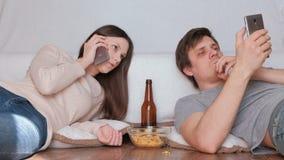 吃芯片的男人和妇女夫妇  妇女谈话手机,浏览他的手机的人 股票录像