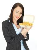 吃芯片的年轻女商人 库存照片