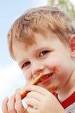吃花生酱三明治的男孩 免版税库存图片