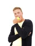 吃英俊的人年轻人的苹果 免版税库存图片