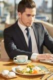 吃英俊的商人午餐 免版税库存图片
