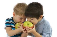 吃苹果的两个男孩 库存图片