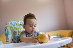 吃苹果的可爱的男婴 婴孩的第一食物10个月 学会小孩的男孩与牙固体食物居住 免版税库存图片