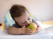 吃苹果的可爱的男婴 婴孩的第一食物10个月 学会小孩的男孩与牙固体食物居住 库存图片