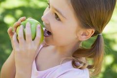 吃苹果的女孩的特写镜头在公园 库存图片